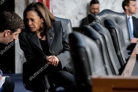 Sen. Kamala Harris, D-Calif., speaks with an aide as Homeland Security Secretary Kirstjen Nielsen and former Homeland Security Secretary Jeh Johnson appear before a Senate Intelligence Committee hearing on election security on Capitol Hill in Washington