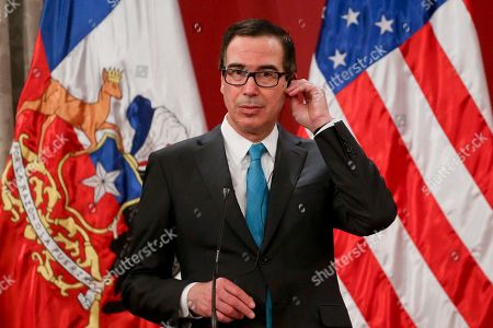 U.S. Treasury Secretary Steven T. Mnuchin places an earbud in his ear as he prepares for a joint press conference at La Moneda presidential palace in Santiago, Chile