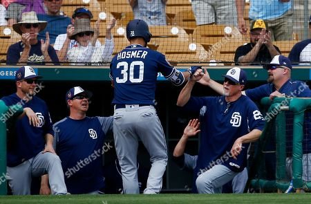 San Diego Padres first baseman Eric Hosmer (30) celebrates his two-run home run against the Chicago White Sox with manager Andy Green, left, bench coach Mark McGwire, second from right, and other coaches during the fifth inning of a spring training baseball game, in Glendale, Ariz. The Padres defeated the White Sox 4-3