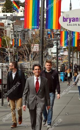 On, San Francisco Mayoral candidate Mark Leno, center, walks in the Castro district of San Francisco on his way to speak to supporters