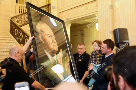 Officials remove the painting of former Sinn Fein Deputy First Minister Martin McGuinness only moments afte it was unveiled by his family in Parliament Buildings, Belfast, Northern Ireland, Britain, 22 March 2018. McGuinness who resigned as deputy First Minister in a protest over the Renewable Heat Incentive scandal, died on 21 March 2017, aged 66.