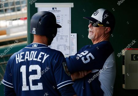 San Diego Padres first baseman Chase Headley (12) talks with bench coach Mark McGwire (25) during the second inning of a spring training baseball game against the Cleveland Indians, in Goodyear, Ariz