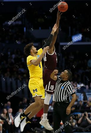 Michigan forward Isaiah Livers, left, and Texas A&M forward Robert Williams reach for the ball during the first half of an NCAA men's college basketball tournament regional semifinal, in Los Angeles