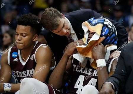 Texas A&M forward Robert Williams, right, covers his face with a towel on the bench during the second half of the team's NCAA men's college basketball tournament regional semifinal against Michigan, in Los Angeles