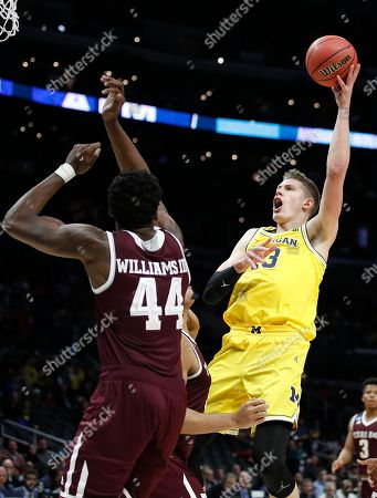 Michigan forward Moritz Wagner, right, shoots against Texas A&M forward Robert Williams (44) during the first half of an NCAA men's college basketball tournament regional semifinal, in Los Angeles