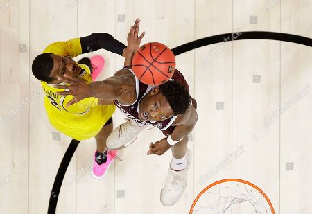 Michigan guard Muhammad-Ali Abdur-Rahkman, left, shoots against Texas A&M forward Robert Williams during the second half of an NCAA men's college basketball tournament regional semifinal, in Los Angeles