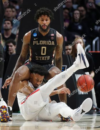Gonzaga forward Johnathan Williams, bottom, reaches for the ball under Florida State forward Phil Cofer (0) during the first half of an NCAA men's college basketball tournament regional semifinal, in Los Angeles