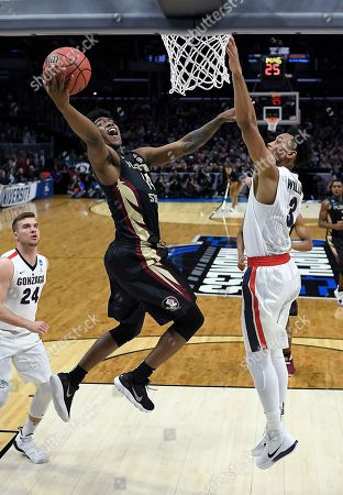 Florida State guard Terance Mann, left, shoots against Gonzaga forward Johnathan Williams (3) during the first half of an NCAA men's college basketball tournament regional semifinal, in Los Angeles