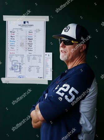 San Diego Padres bench coach Mark McGwire stands in the dugout during the second inning of a spring training baseball game against the Cleveland Indians, in Goodyear, Ariz. The Padres defeated the Indians 7-6