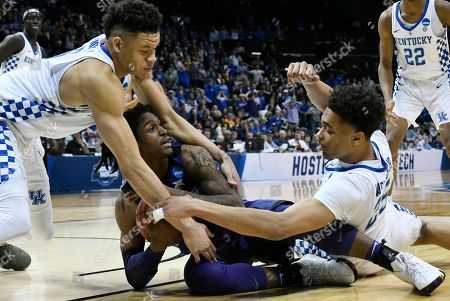 Kansas State guard Cartier Diarra (2) holds onto the ball as Kentucky's PJ Washington (25) and Kevin Knox (5) defend during the second half of a regional semifinal NCAA college basketball tournament game, in Atlanta. Kansas State won 61-58