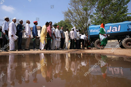 Indian activists wait in a queue to fill up their bottles from a water tanker as they are present to support Indian veteran social activist Anna Hazare (Unseen) who is sitting on an indefinite hunger strike at Ramlila Maidan, in New Delhi, India, 23 March 2018. According to a news report, Anna Hazare is on an indefinite hunger strike as he demands for a stronger Lokpal or Anti-graft bill and better conditions for farmers in India.