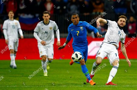 Brazil's Douglas Costa fights for the ball with Russia's Vladimir Granat, right, during an international friendly soccer match between Russia and Brazil at the Luzhniki stadium in Moscow, Russia