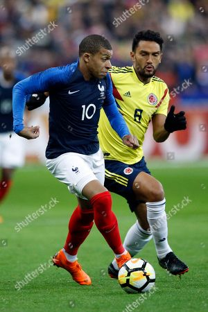 France's Kylian Mbappe, left, competes with Colombia's Abel Aguilar during a friendly soccer match between France and Colombia, at the Stade de France stadium in Saint-Denis, outside Paris, France