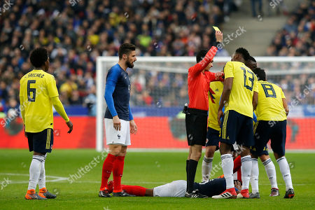 Swiss referee Adrien Jaccottet gives a yellow card to Colombia's Abel Aguilar, right, as Feyenoord's Nicolai Jorgensen, second left, looks on during a friendly soccer match between France and Colombia in Saint-Denis, outside Paris