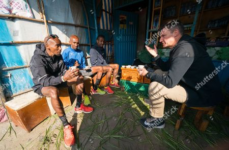 Mo Farah (UK) in sun glasses having a morning coffee with Gary Lough (UK) his new coach and training partners Abdi Abdirahman (USA) in blue and Bashir Abdi (BEL) in black in Sulultra near Addis Ababa in Ethiopia.