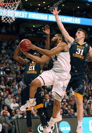 Omari Spellman, Wesley Harris, Logan Routt. Villanova's Omari Spellman drives to the basket between West Virginia's Wesley Harris, left, and Logan Routt during the second half of an NCAA men's college basketball tournament regional semifinal, in Boston