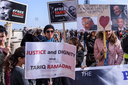 People hold placards which read 'Justice and Dignity for Tariq Ramadan' and 'Free Tariq Ramadan' during a gathering in support of Islamic scholar Tariq Ramadan, in Paris, France, 24 March 2018. Tariq Ramadan is detained in France on alleged sexual harassment and rape charges. Ramadan is detained for questioning in Paris, months after women filed rape charges or sexual assault against him in France. Ramadan has denied the allegations.