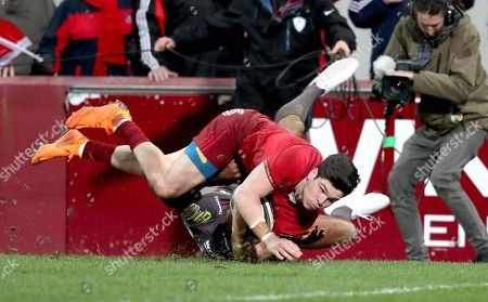 Munster vs Scarlets . Munster's Alex Wootton scores a try despite the efforts from Tom Varndell of the Scarlets
