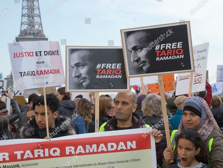 """Supporters of Muslim scholar Tariq Ramadan stage a protest near the Eiffel Tower in Paris, France, . Prominent Muslim scholar Tariq Ramadan is being held in jail after he was handed preliminary rape charges based on allegations from two women. Placard left reads, """"Justice and Dignity for Tariq Ramadan"""