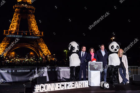 The mayor of Paris Anne Hidalgo (C) and WWF France head Pascal Canfin (C-R) attend with other personalities at the WWF Earth Hour event where she symbolically extinguishes the light of the Eiffel Tower in Paris, France, 24 March 2018. Earth Hour is an annual event in which lights are switched off in major cities around the world to draw attention to energy consumption and its environmental effects. The aim is to give people a voice on the planet's future and an opportunity to work together to create a sustainable low carbon future for planet earth.