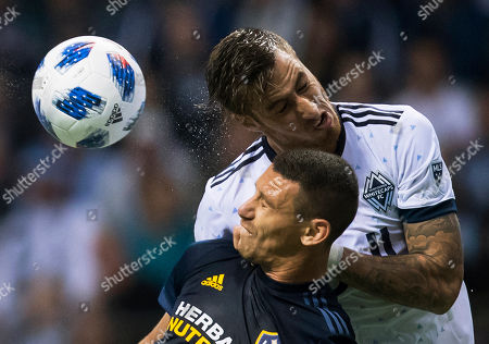 Jose Aja, Daniel Steres. Vancouver Whitecaps' Jose Aja, back, and Los Angeles Galaxy's Daniel Steres vie for a head ball during the first half of an MLS soccer match in Vancouver, British Columbia