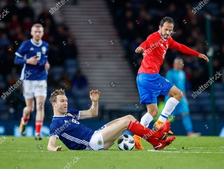 Marco Urena of Costa Rica beaten to the ball by Kevin McDonald of Scotland
