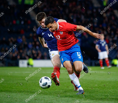 Daniel Colindres of Costa Rica chased by Grant Hanley of Scotland