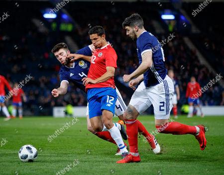 Daniel Colindres of Costa Rica between Grant Hanley & Callum Paterson of Scotland