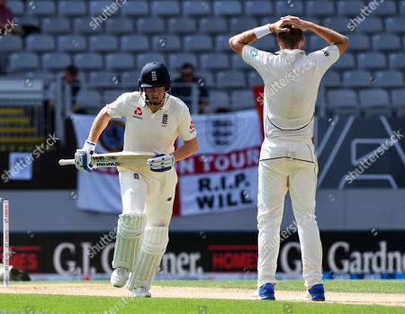 England's Jonathan Bairstow, left, runs past New Zealand's Tim Southee dropping a catch during their first cricket test in Auckland, New Zealand