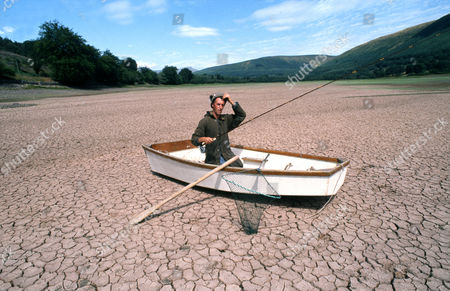 Reservoir during a severe drought - man in a boat attempting to fish