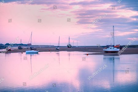 Boats sit on the mud flats in the harbour at dawn, Wells Next The Sea in Norfolk.