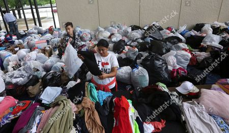 Volunteers Brenda Tcoc, right, and Hugo Wilson help sort bags of donated clothes for victims of the flooding from Tropical Storm Harvey after a shelter opened at the Lakewood Church in Houston, Texas