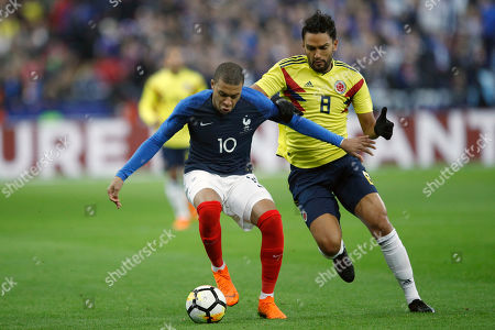 France's Kylian Mbappe, left, challenges for the ball with Colombia's Abel Aguilar during a friendly soccer match between France and Colombia at the Stade de France stadium in Saint-Denis, outside Paris, France