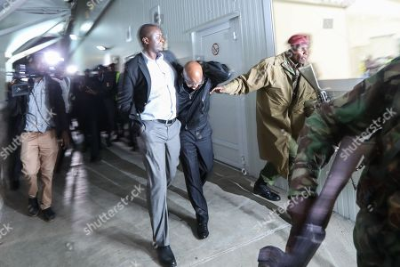 Kenyan business man and an opposition supporter Jimmy Wanjigi (C) covers himself as he runs away from paramilitary police after Kenyan lawyer and opposition figure Miguna Miguna (not pictured) was detained at immigration upon his arrival at the Jomo Kenyatta International Airport in Nairobi, Kenya, 26 March 2018. Miguna who was traveling on his Canadian passport, was blocked from entering the country and deported back to Dubai after he refused to apply for a Kenyan visa upon his arrival. Paramilitary police were deployed at the airport to disperse opposition supporters and journalists using force that left some journalists injured. The government on 07 February deported Miguna to Canada, disobeying five court orders to release him or produce him in court after arresting him for taking part in a mock ?swearing-in? ceremony of the opposition leader Raila Odinga, who since has agreed to work with his rival President Uhuru Kenyatta. The High Court on 15 February ruled Miguna?s deportation illegal.