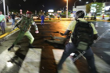 A picture taken with slow shutter effect shows, a Kenyan paramilitary police (L) runs after a journalist (R) as he disperses them together with opposition supporters after a Kenyan lawyer and opposition figure Miguna Miguna (not pictured) was detained at immigration upon his arrival at the Jomo Kenyatta International Airport in Nairobi, Kenya, 26 March 2018. Miguna who was traveling on his Canadian passport, was blocked from entering the country and deported back to Dubai after he refused to apply for a Kenyan visa upon his arrival. Paramilitary police were deployed at the airport to disperse opposition supporters and journalists using force that left some journalists injured. The government on 07 February deported Miguna to Canada, disobeying five court orders to release him or produce him in court after arresting him for taking part in a mock ?swearing-in? ceremony of the opposition leader Raila Odinga, who since has agreed to work with his rival President Uhuru Kenyatta. The High Court on 15 February ruled Miguna?s deportation illegal.
