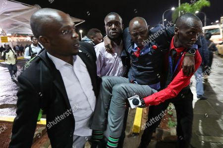 A Kenyan journalist (C) is carried by other journalists to the hospital after he was injured by paramilitary police officers as they dispersed them together with opposition supporters after a Kenyan lawyer and opposition figure Miguna Miguna (not pictured) was detained at immigration upon his arrival at the Jomo Kenyatta International Airport in Nairobi, Kenya, 26 March 2018. Miguna who was traveling on his Canadian passport, was blocked from entering the country and deported back to Dubai after he refused to apply for a Kenyan visa upon his arrival. Paramilitary police were deployed at the airport to disperse opposition supporters and journalists using force that left some journalists injured. The government on 07 February deported Miguna to Canada, disobeying five court orders to release him or produce him in court after arresting him for taking part in a mock ?swearing-in? ceremony of the opposition leader Raila Odinga, who since has agreed to work with his rival President Uhuru Kenyatta. The High Court on 15 February ruled Miguna?s deportation illegal.