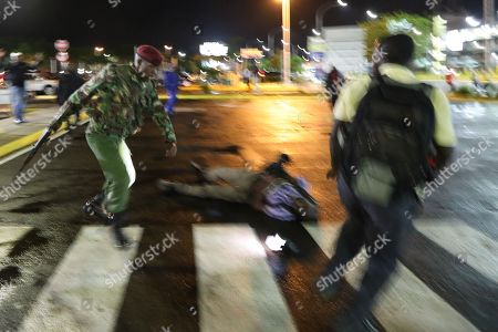 A picture taken with slow shutter effect shows, a Kenyan paramilitary police (L) running after a journalist (R) after injuring another (C) as he disperses them together with opposition supporters after a Kenyan lawyer and opposition figure Miguna Miguna (not pictured) was detained at immigration upon his arrival at the Jomo Kenyatta International Airport in Nairobi, Kenya, 26 March 2018. Miguna who was traveling on his Canadian passport, was blocked from entering the country and deported back to Dubai after he refused to apply for a Kenyan visa upon his arrival. Paramilitary police were deployed at the airport to disperse opposition supporters and journalists using force that left some journalists injured. The government on 07 February deported Miguna to Canada, disobeying five court orders to release him or produce him in court after arresting him for taking part in a mock ?swearing-in? ceremony of the opposition leader Raila Odinga, who since has agreed to work with his rival President Uhuru Kenyatta. The High Court on 15 February ruled Miguna?s deportation illegal.