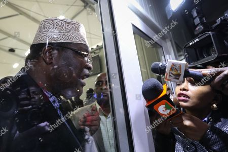 Kenyan lawyer and opposition figure Miguna Miguna (L) addresses journalists (R) from a closed door after he was detained at immigration upon his arrival at the Jomo Kenyatta International Airport in Nairobi, Kenya, 26 March 2018. Miguna who was traveling on his Canadian passport, was blocked from entering the country and deported back to Dubai after he refused to apply for a Kenyan visa upon his arrival. Paramilitary police were deployed at the airport to disperse opposition supporters and journalists using force that left some journalists injured. The government on 07 February deported Miguna to Canada, disobeying five court orders to release him or produce him in court after arresting him for taking part in a mock ?swearing-in? ceremony of the opposition leader Raila Odinga, who since has agreed to work with his rival President Uhuru Kenyatta. The High Court on 15 February ruled Miguna?s deportation illegal.