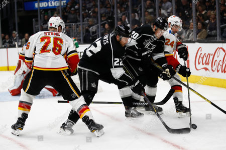 Trevor Lewis, Tanner Pearson, Michael Stone, Travis Hamonic. Los Angeles Kings' Tanner Pearson(70) and Trevor Lewis(22) fight for the puck with Calgary Flames' Michael Stone (26) and Travis Hamonic (24) during the second period of an NHL hockey game, in Los Angeles