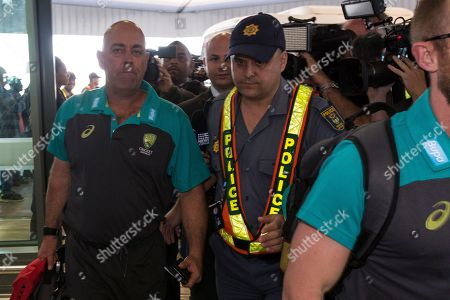 Australian cricket coach Darren Lehmann, left, arrives with his team at the Cape Town International airport as they depart to Johannesburg for the final five day cricket test match, in Cape Town, South Africa, . Australia skipper Steve Smith has been suspended by the International Cricket Council for the match for his part in a ball tampering scandal during the third test. Smith admitted some senior players were aware of the tampering attempt