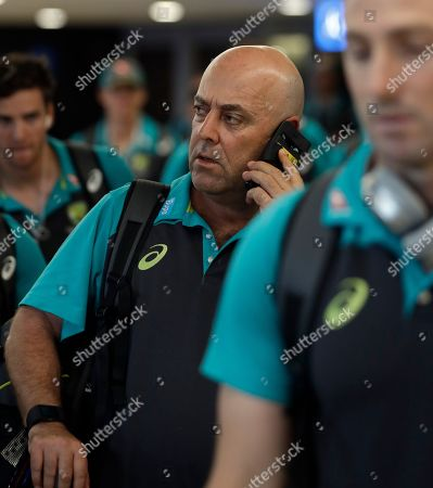 Australia's coach Darren Lehmann talks on the phone, after the arrival of the Australian team to OR Tambo International International airport in Johannesburg, South Africa, . Australia skipper Steve Smith has been suspended by the International Cricket Council for the fourth test match against South Africa for his part in a ball tampering scandal during the third test. Smith admitted some senior players were aware of the tampering attempt