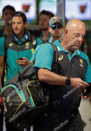 Australia's coach Darren Lehmann walks after the arrival of the Australian team to OR Tambo International International airport in Johannesburg, South Africa, . Australia skipper Steve Smith has been suspended by the International Cricket Council for the fourth test match against South Africa for his part in a ball tampering scandal during the third test. Smith admitted some senior players were aware of the tampering attempt