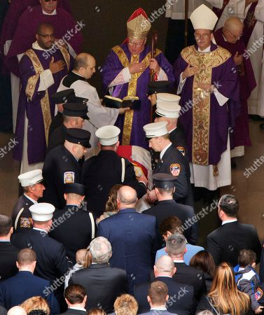 Archbishop Timothy Dolan, center, presides over the casket of New York City firefighter Michael Davidson as it enters St. Patrick's Cathedral, in New York, . Davidson died early Friday battling a fierce blaze on a movie set after getting separated from his fellow firefighters in the thick smoke