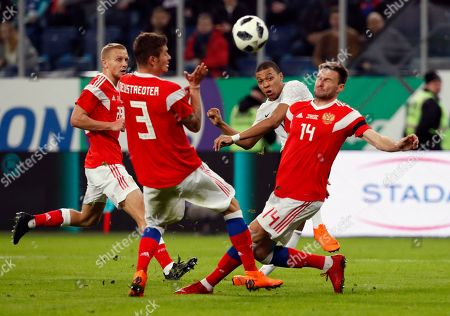 Kylian Mbappe (2-R) of France in action against Roman Neustadter (2-L) and Vladimir Granat (R) of Russia during an international friendly soccer match between Russia and France at the Zenit Arena in St. Petersburg, Russia, 27 March 2018.