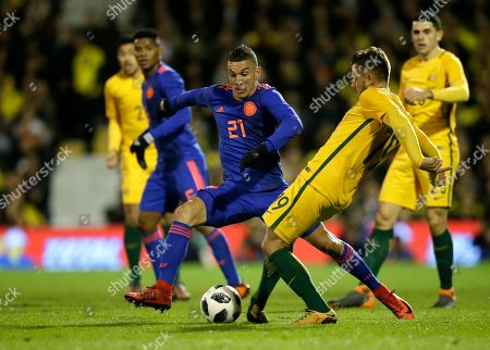 Colombia's Mateus Uribe, center, duels for the ball with Australia's Josh Risdon during a friendly soccer match between Colombia and Australia at Craven Cottage stadium in London