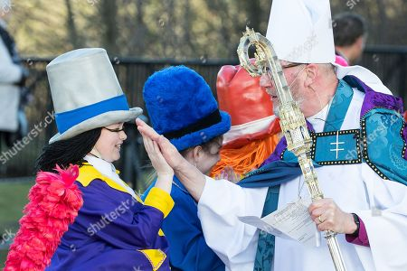 Children dressed as Diddy Men line up outside Liverpool Cathedral after the service and high five a clergyman