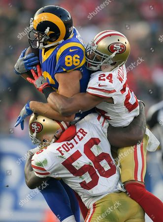 Los Angeles Rams tight end Derek Carrier, top, is tackled by San Francisco 49ers outside linebacker Reuben Foster and defensive back K'Waun Williams (24) during the second half of an NFL football game, in Los Angeles