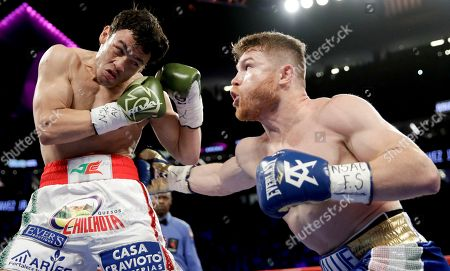 Canelo Alvarez, right, of Mexico, hits Julio Cesar Chavez Jr., of Mexico, during their catch weight boxing match, in Las Vegas