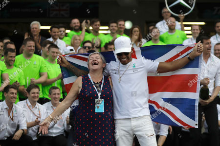 Mercedes driver Lewis Hamilton, of Britain, celebrates with his mother Carmen Larbalestier at the pit lane after the Formula One Mexico Grand Prix auto race at the Hermanos Rodriguez racetrack in Mexico City, . Hamilton won his fourth career Formula One season championship on Sunday with a ninth-place finish at the Mexican Grand Prix in a race won by Red Bull's Max Verstappen