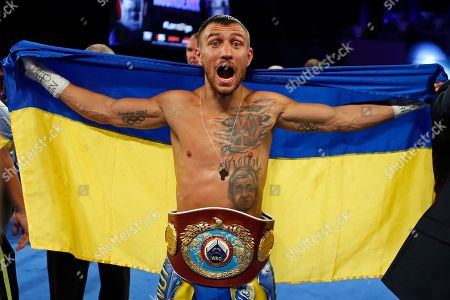 Vasyl Lomachenko, of Ukraine, celebrates after defeating Guillermo Rigondeaux during a WBO junior lightweight title boxing match, in New York
